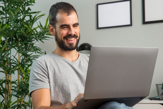 Homem sorridente trabalhando em casa em um laptop