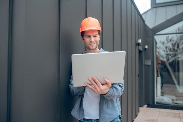 Homem sorridente trabalhando em um laptop ao ar livre
