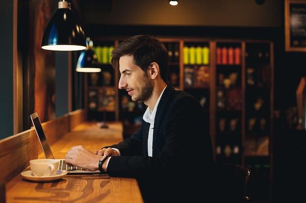 Homem sorridente, trabalhando no laptop, tomando café
