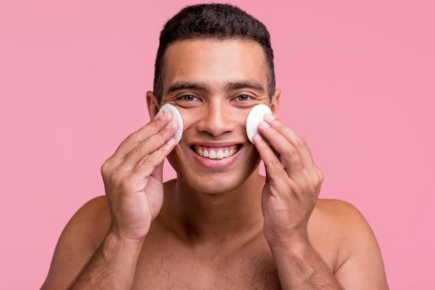 Homem sorridente usando almofadas de algodão no rosto