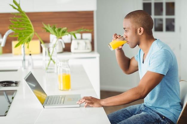 Homem sorridente usando laptop e beber suco de laranja na cozinha