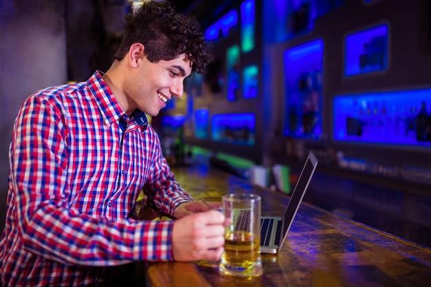 Homem sorridente usando laptop no balcão de bar