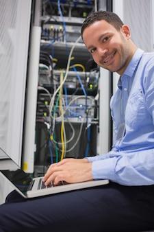 Homem sorridente usando o laptop ao lado de servidores