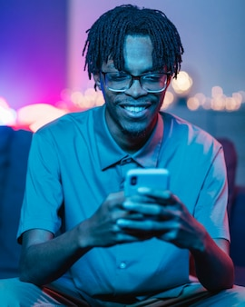Homem sorridente usando seu smartphone enquanto está em casa