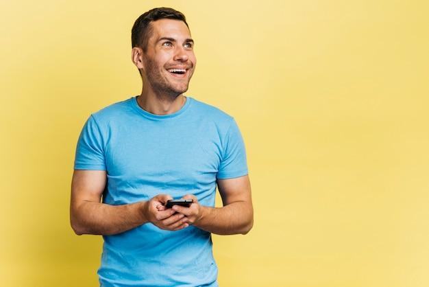 Homem sorridente usando seu telefone