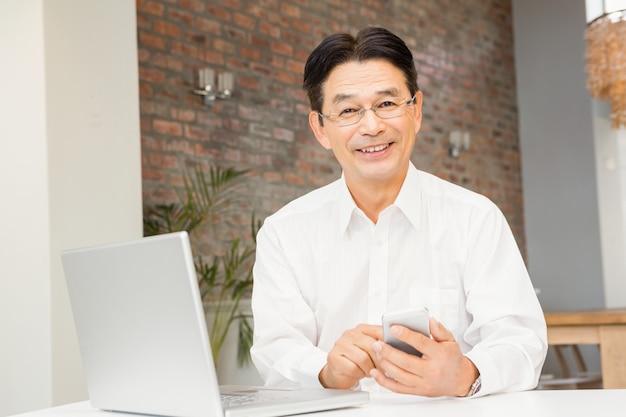 Homem sorridente, usando, smartphone, e, laptop, em, sala de estar