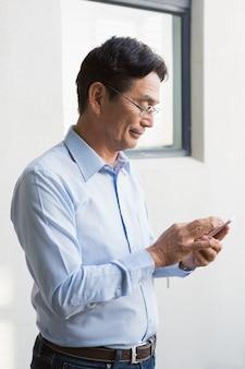 Homem sorridente usando smartphone em casa