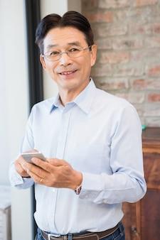 Homem sorridente usando smartphone em pé em casa
