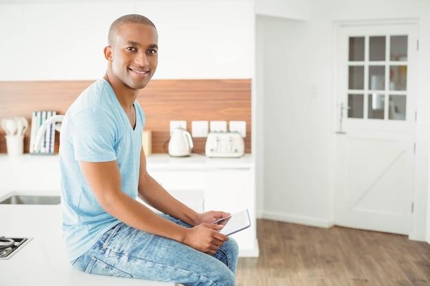 Homem sorridente usando tablet na cozinha sentado no balcão