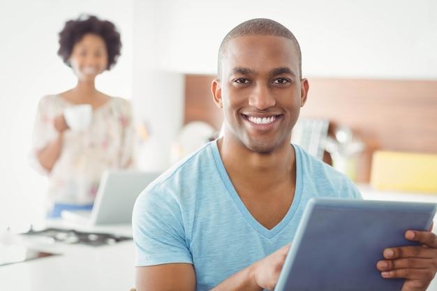 Homem sorridente usando tablet na cozinha