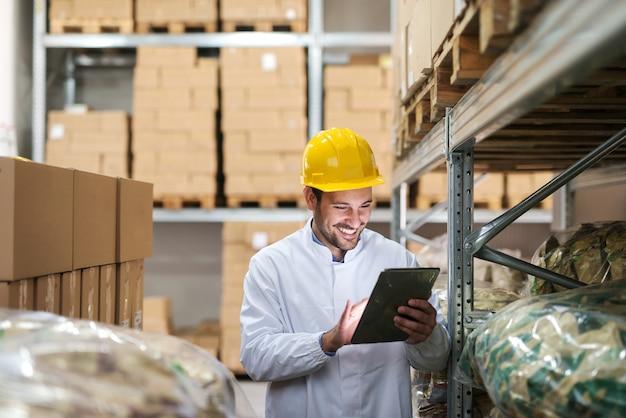 Homem sorridente usando tablet no armazém.