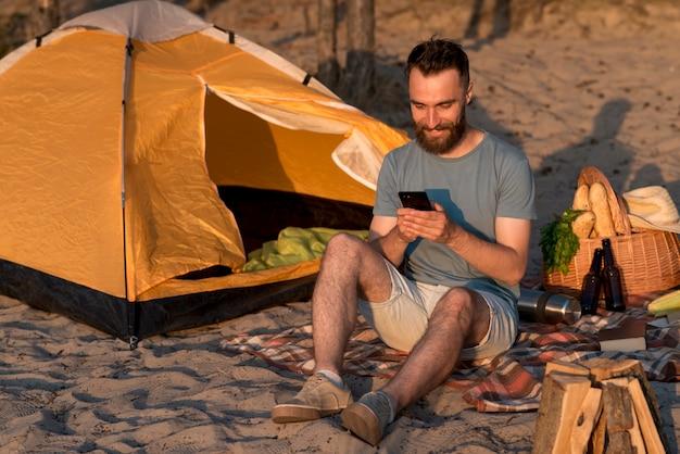 Homem sorridente, verificando seu smartphone