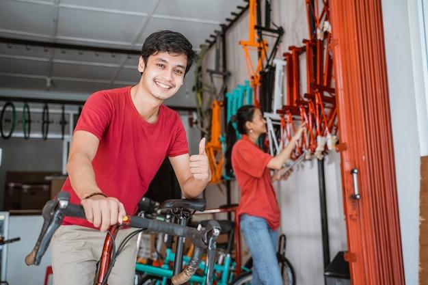 Homem sorrindo com o polegar para cima na loja de bicicletas