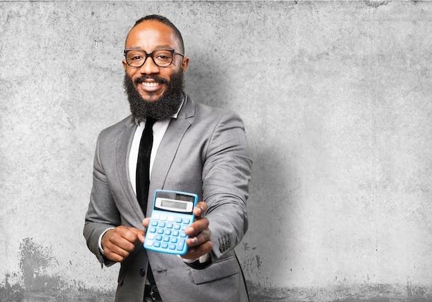 Homem sorrindo com uma calculadora