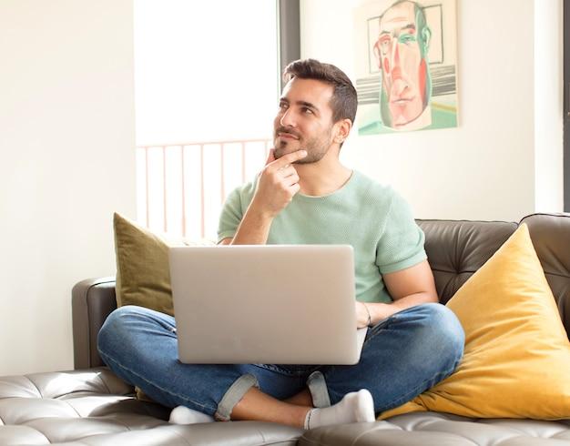 Homem sorrindo com uma expressão feliz e confiante com a mão no queixo, pensando e olhando para o lado