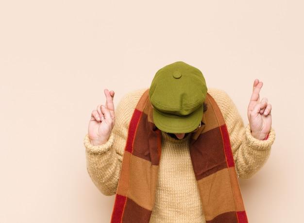 Homem sorrindo e cruzando ansiosamente os dois dedos, sentindo-se preocupado e desejando ou esperando boa sorte