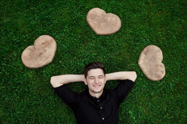 Homem sorrindo e curtindo o dia de verão na grama entre dois corações de madeira