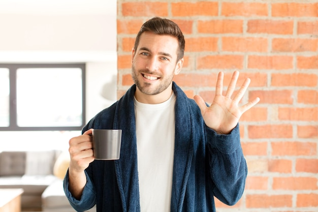 Homem sorrindo e homem parecendo amigável, mostrando o número cinco ou quinto com a mão para a frente, em contagem regressiva