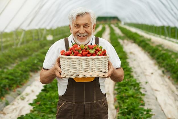 Homem sorrindo e segurando uma cesta de morangos frescos