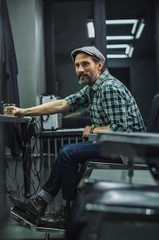 Homem sorrindo e virando a cabeça enquanto está sentado na barbearia