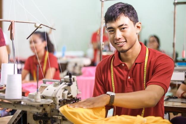Homem sorrindo enquanto costura em um sewinghine em uma fábrica de roupas