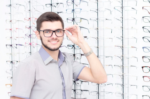 Homem sorrindo enquanto experimentava óculos na loja