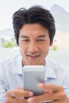 Homem sorrindo enviando uma mensagem de texto