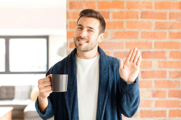 Homem sorrindo feliz e alegre, acenando com a mão, dando as boas-vindas e cumprimentando você ou dizendo adeus