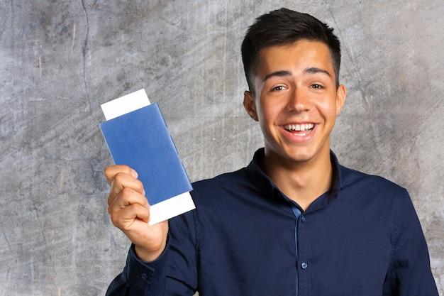 Homem, sorrindo, olhando câmera, e, segurando, bilhetes, com, passaporte