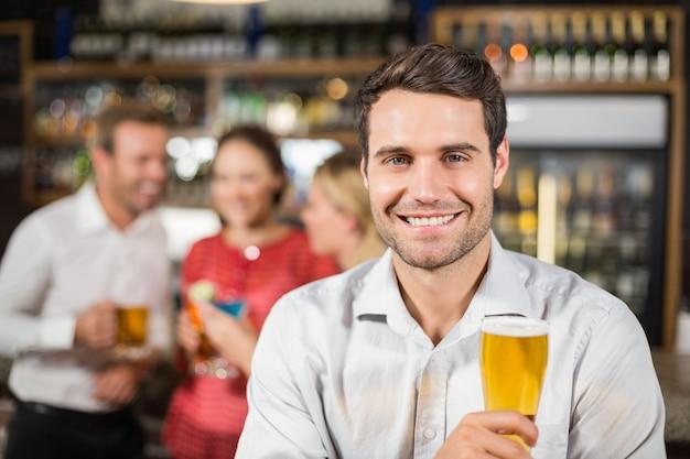 Homem sorrindo para a câmera segurando uma cerveja
