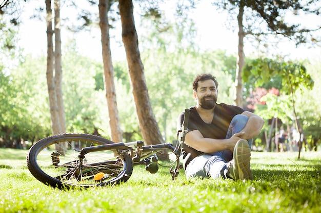 Homem sorrindo para a câmera sentado no chão na grama em um parque ao lado de sua bicicleta