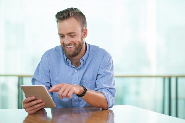 Homem sorrindo sentado à tabela do café e que usa a tabuleta