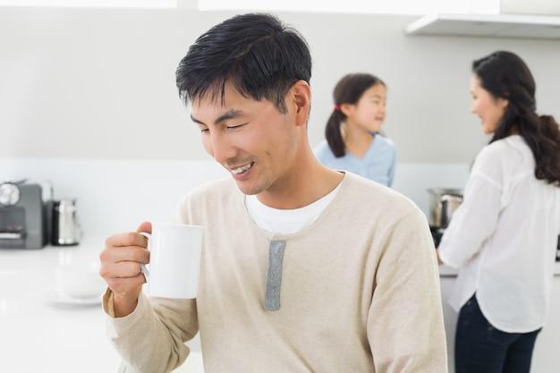 Homem sorrindo tomando café com a família em segundo plano