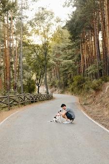 Homem sozinho beijando, abraçando e acariciando seu cão labrador preto e branco de membro da família na estrada na floresta de pinheiros sob a luz do sol da noite