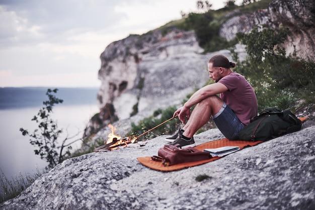 Homem sozinho sentado perto da fogueira, tentando manter o fogo na borda da montanha.