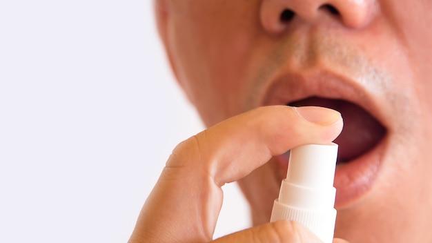 Homem spay medicamentos orais reduzir a tosse em fundo branco