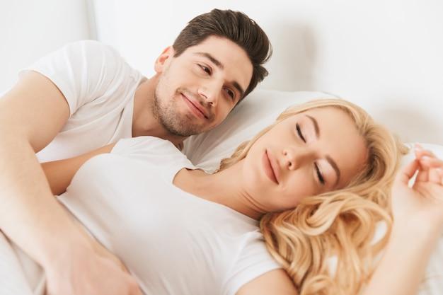 Homem sua esposa perto encontra-se na cama dormindo