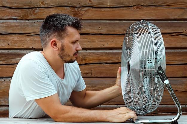 Homem suado na frente de um ventilador de refrigeração