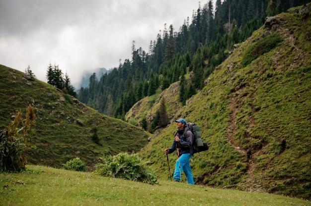 Homem subindo a colina com caminhadas mochila e paus