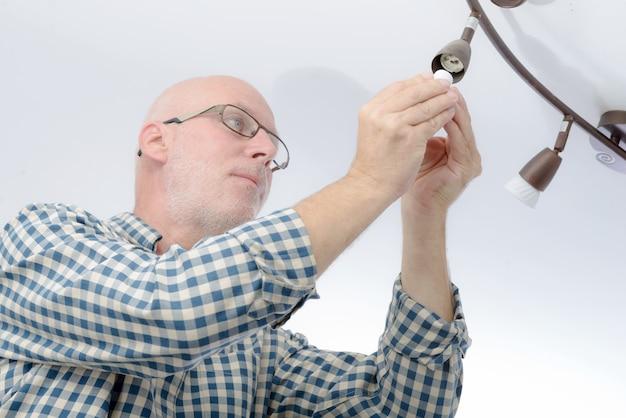 Homem substituindo a lâmpada em casa