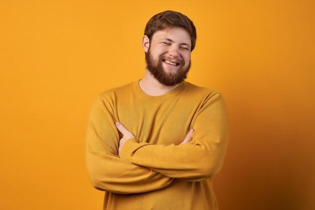 Homem sueco atraente com barba e cabelo elegante, ri de uma história engraçada de um amigo com as mãos cruzadas e os olhos fechados.