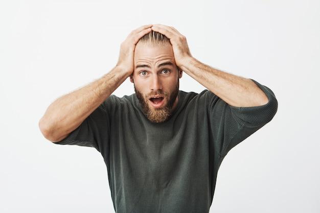 Homem sueco bonito com penteado na moda e barba de mãos dadas na cabeça chocado