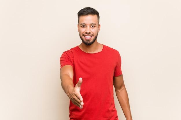 Homem sul-asiático novo que estica a mão na câmera no gesto de cumprimento.