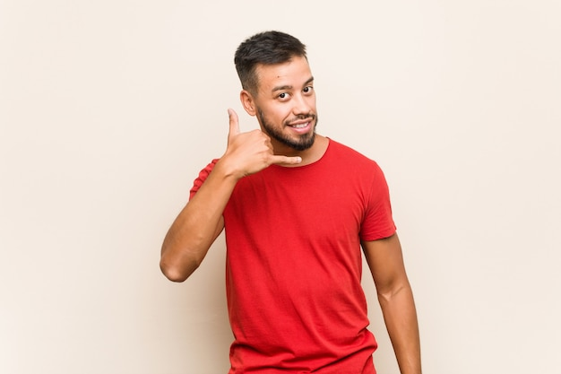 Homem sul-asiático novo que mostra um gesto de chamada de telefone móvel com os dedos.