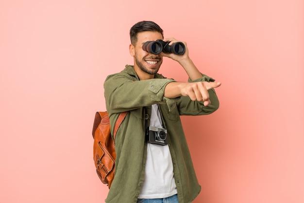Homem sul-asiático novo que olha com binóculos.