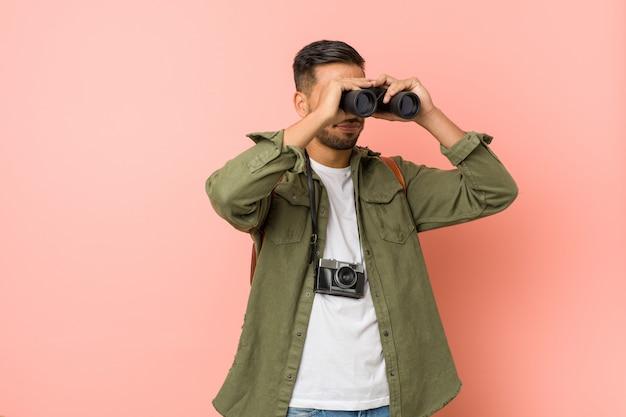 Homem sul asiático novo que olha com binóculos.