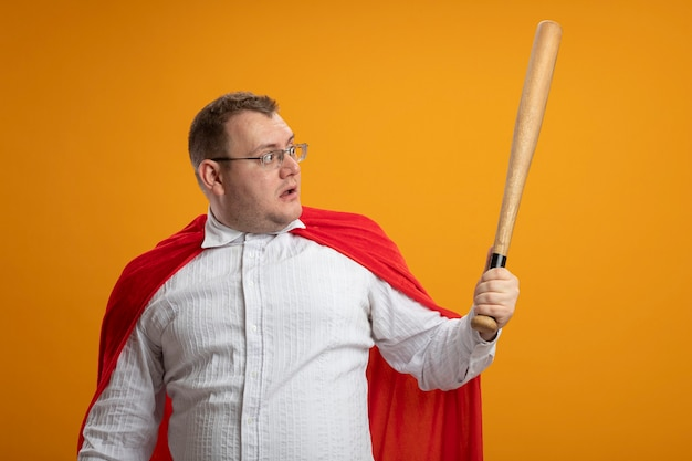 Homem super-herói adulto impressionado com capa vermelha usando óculos segurando e olhando para o taco de beisebol isolado na parede laranja