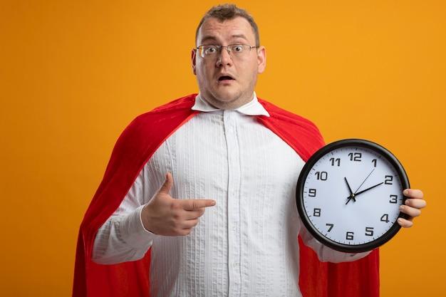 Homem super-herói adulto impressionado com uma capa vermelha e óculos, olhando para a frente, segurando e apontando para o relógio isolado na parede laranja