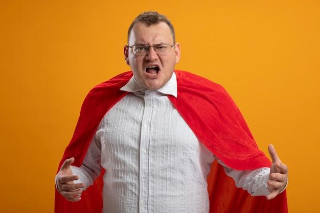 Homem super-herói adulto zangado com capa vermelha usando óculos e mantendo as mãos no ar, olhando para a frente, isolado na parede laranja