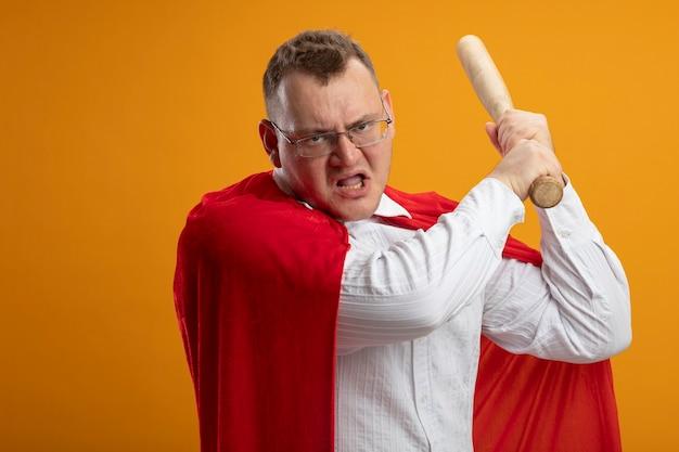 Homem super-herói adulto zangado com capa vermelha usando óculos segurando um taco de beisebol olhando para a frente se preparando para bater isolado na parede laranja